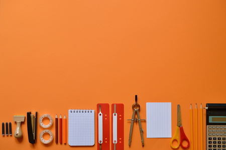 Office or school supplies on orange paper board