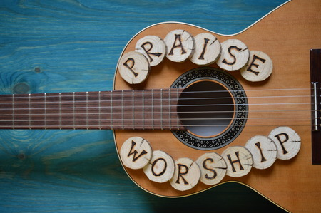 guitar on teal wooden background with wood pieces on it lettering the words: PRAISE and WORSHIP