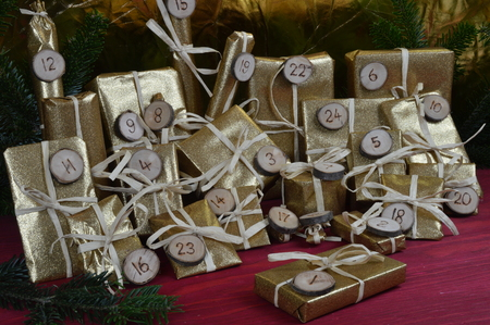 tinkered: advent calendar with twenty four golden presents on red wood Stock Photo