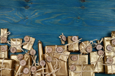 tinkered: Border of advent calendar with twenty four golden presents on teal wood with negative space above
