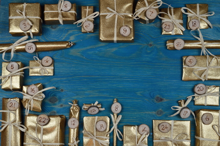 tinkered: Frame of advent calendar with twenty four golden presents on teal wood