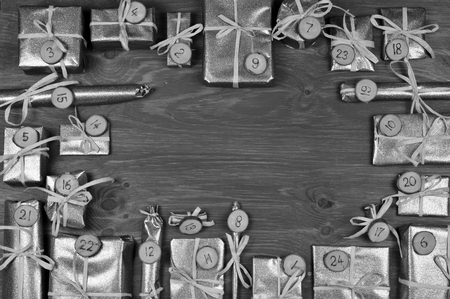 tinkered: Frame of advent calendar with twenty four silver presents on gray wood Stock Photo