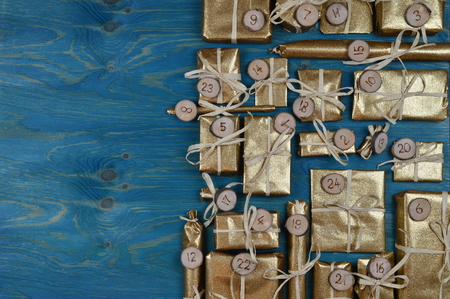 tinkered: Border of advent calendar with twenty four golden presents on teal wood with negative space to the left