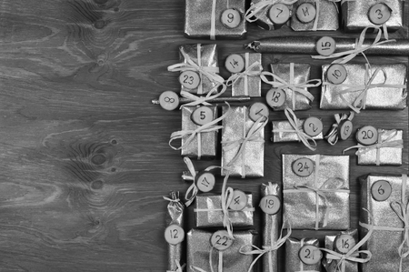 tinkered: Border of advent calendar with twenty four silver presents on gray wood with negative space to the left Stock Photo