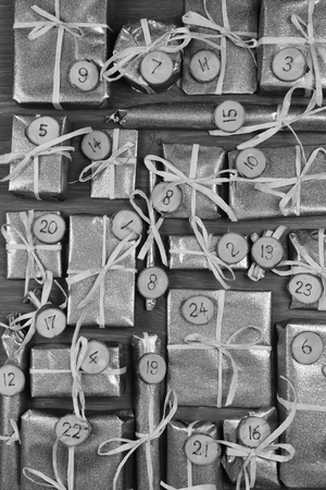 tinkered: Advent calendar with twenty four silver presents on gray wood Stock Photo