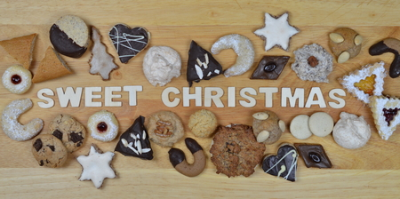 opulence: different kinds of Christmas cookies on a breadboard around the words: SWEET CHRISTMAS Stock Photo
