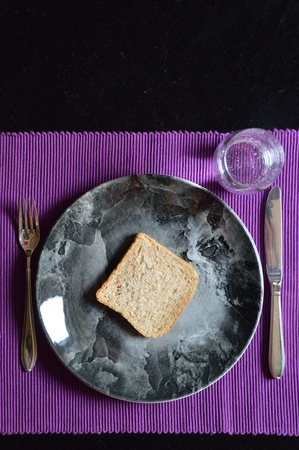 waive: reduced meal in Lent with a slice of bread on a plate and a glass of water