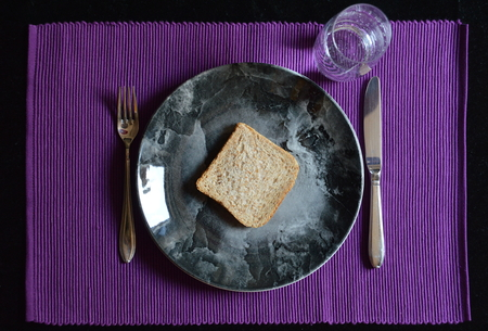 renounce: reduced meal in Lent with a slice of bread on a plate and a glass of water