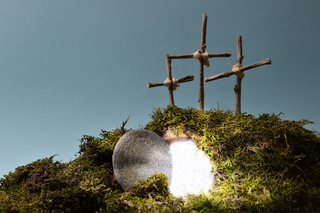 resurrection garden as easter decoration with a stone near the empty tomb filled with blinding light and three crosses on a hill above Stock Photo