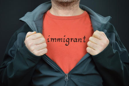 he is different: a man showing his t-shirt with the word immigrant on it