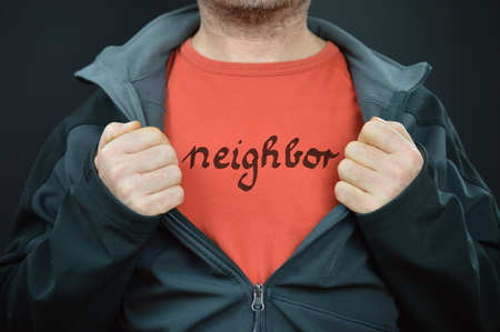 confiding: a man showing his t-shirt with the word neighbor on it