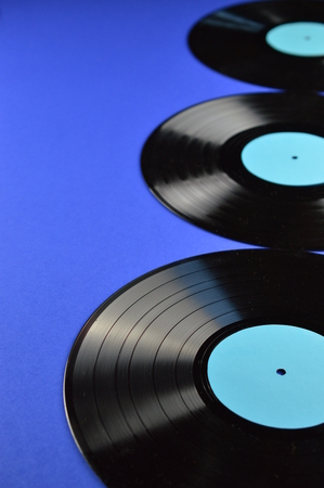 conceptional: three old black vinyl records with blank labels cyan on blue background Stock Photo