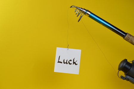 paper with the word LUCK written on at the fishhook Stock Photo
