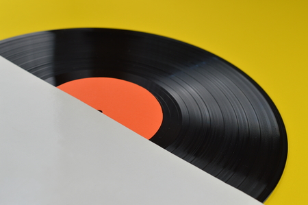 conceptional: old black vinyl record with blank label orange halfway out of its white blank cover on yellow background