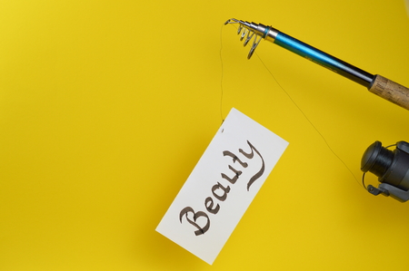Temptation ? ? a piece of paper with the word BEAUTY written on the fishhook of an angling rod