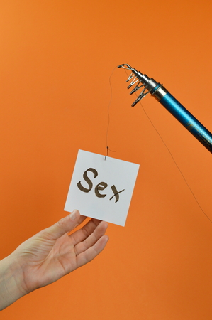 A hand grabbing a piece of paper with the word SEX written on a dangling from a fishing pole Stock Photo