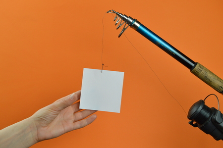 A hand grabbing a blank piece of paper dangling from a fishing pole