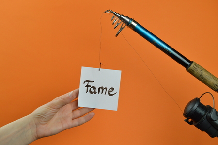 A hand grabbing a piece of paper with the word FAME written on a dangling from a fishing pole Stock Photo