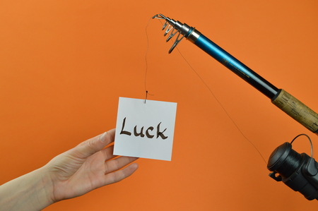 A hand grabbing a piece of paper with the word LUCK written on dangling from a fishing pole Stock Photo