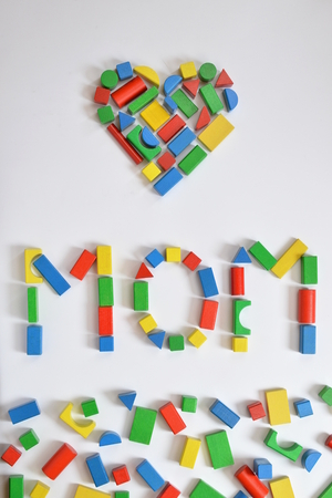 assembled: Colorful wooden toy blocks lettering the word MOM and a heart on white background Stock Photo