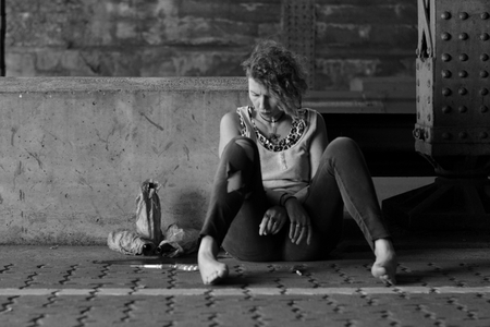 A stressed punk woman under a bridge with bottles of alcohol and other drugs around her
