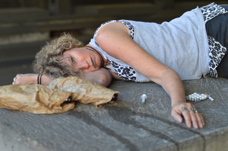 A drunk, homeless woman sleeping under a bridge with bottles of alcohol and other drugs around her