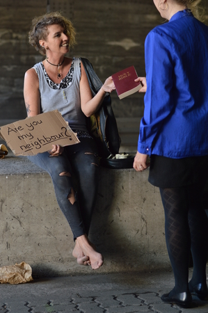 A punk woman sitting under a bridge with bottle of alcohol next by holding a sign and getting a bible from a businesswoman Stock Photo