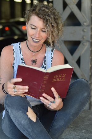 A punk woman sitting under a bridge and reading a Bible thrilled