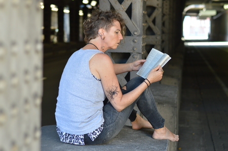 A punk woman sitting under a bridge and reading a Bible surprised