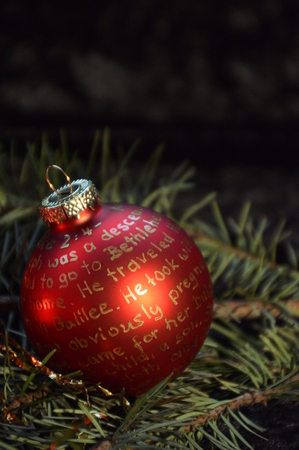 testament schreiben: the nativity story selfmade written in golden letters on red christmas ornament bulb