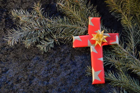 cross wrapped in fancy paper between fig branches as a present at Christmas day