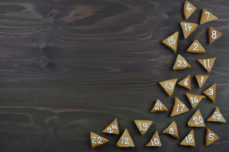 border of 25 numbered advent cookies on brown wood with copyspace