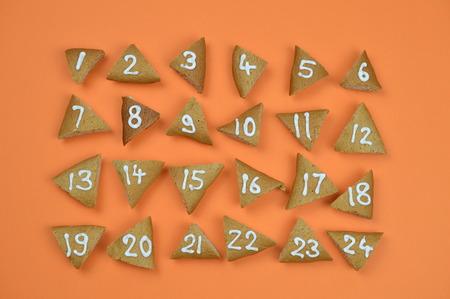 twenty-four numbered and sorted advent cookies on orange background Stock Photo