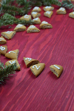 twenty-four numbered advent cookies on red wood with pine boughs Stock Photo