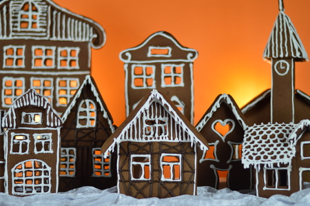 home made gingerbread village in front of orange background on white snowlike velvet