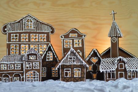 home made gingerbread village in front of wooden background on white snowlike velvet Stok Fotoğraf