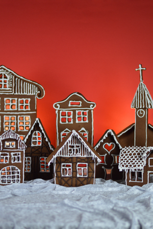 home made gingerbread village in front of red background on white snowlike velvet