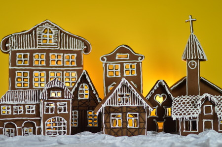 home made gingerbread village in front of yellow background snowlike velvet as advent decoration