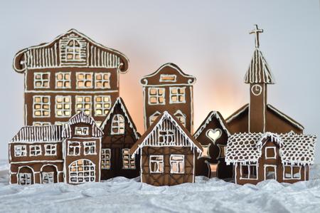 Homemade gingerbread village in front of white background on white snowlike velvet as decoration for Christmas