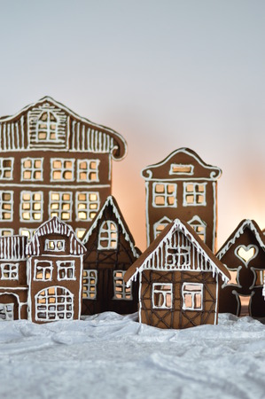 home made gingerbread village in front of white background on white snowlike velvet as decoration for christmas