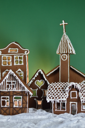 home made traditional sweet gingerbread village in front of green background on white snowlike velvet