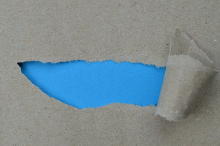 ripped paper revealing blue blank space for a message