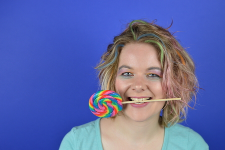Portrait of a young blond woman with colorful hair and a big lollipop between her teeth having fun and looking into the camera