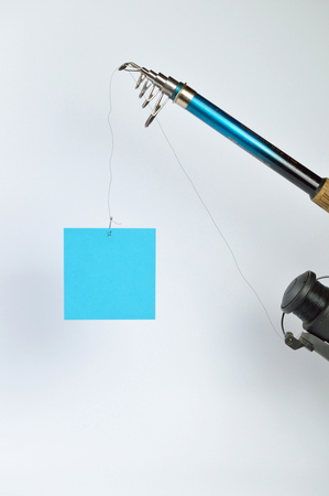 a blank piece of cyan paper at the fishhook of an angling rod