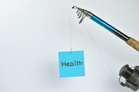 the word HEALTH on a cyan piece of paper hanging from a fishing line Stock Photo