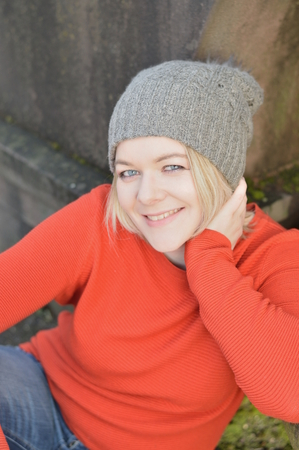 young pretty blond woman with orange sweater and gray kneeling outdoors sitting in a park leaning against a stone and smiling Imagens