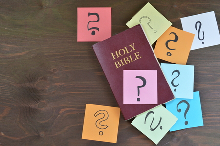 Holy bible and colorful note pads with question mark on brown wood 写真素材