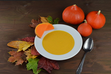 autumnal pumpkin soup in a bowl with hokkaido pumpkin leaves and a spoon on a brown wooden table