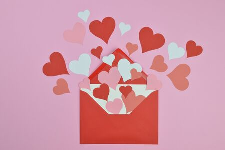 white blank letter in open red envelope with lots of red, pink and white hearts