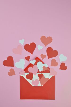 white blank letter in open red envelope with pink and white paper hearts Stockfoto